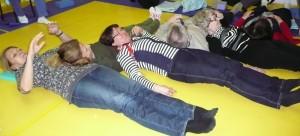 """""""Madon"""" alkupää naurujoogassa. """"Mato"""" muodostettiin siten, että osanottajat käydessään lattialle makuulle panivat päänsä edellisen makuulla olijan vatsan päälle."""