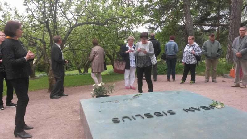 Ainolan puutarhassa sijaitsevan pronssisen hautapaaden on suunnitellut Sibeliusten vävy arkkitehti Aulis Blomstedt. Vasemmalla opas Tuula Vartiainen.
